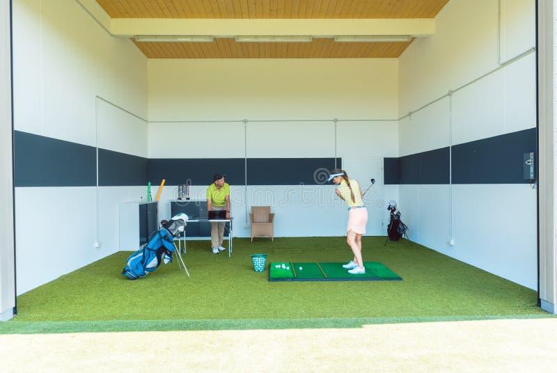 使用现代设备的热忱的高尔夫球教练,当教年轻女人时 免版税库存照片