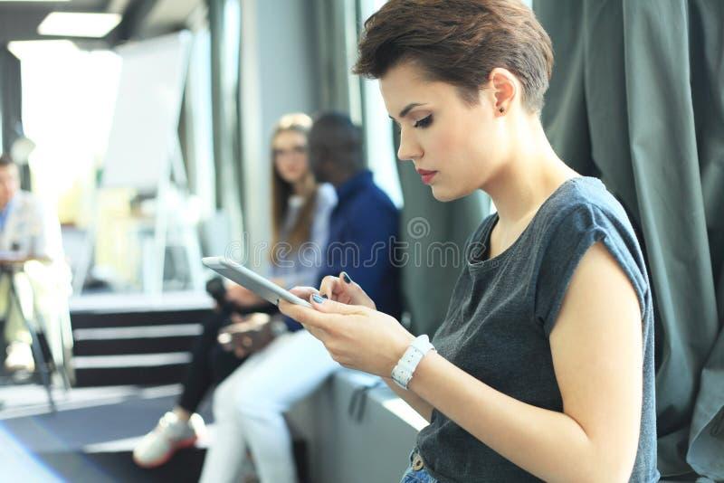 使用现代智能手机手的画象年轻女商人 女孩读书sms消息在运作的过程中在晴朗的办公室 免版税库存照片