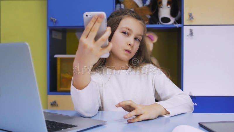 使用现代智能手机的逗人喜爱的小女孩 库存图片
