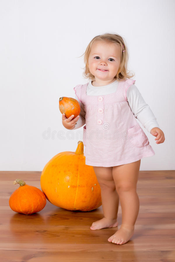 使用用一个巨大的南瓜的滑稽的笑的女婴 库存图片