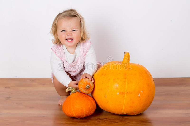 使用用一个巨大的南瓜的滑稽的笑的女婴 免版税图库摄影