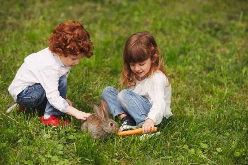 使用用兔子的男孩和女孩在公园 图库摄影