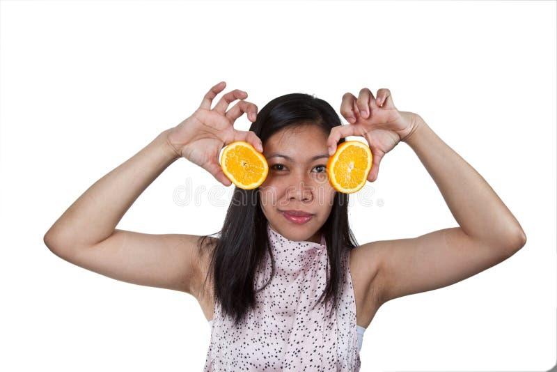 使用用桔子的一个亚裔女孩的画象 免版税库存照片