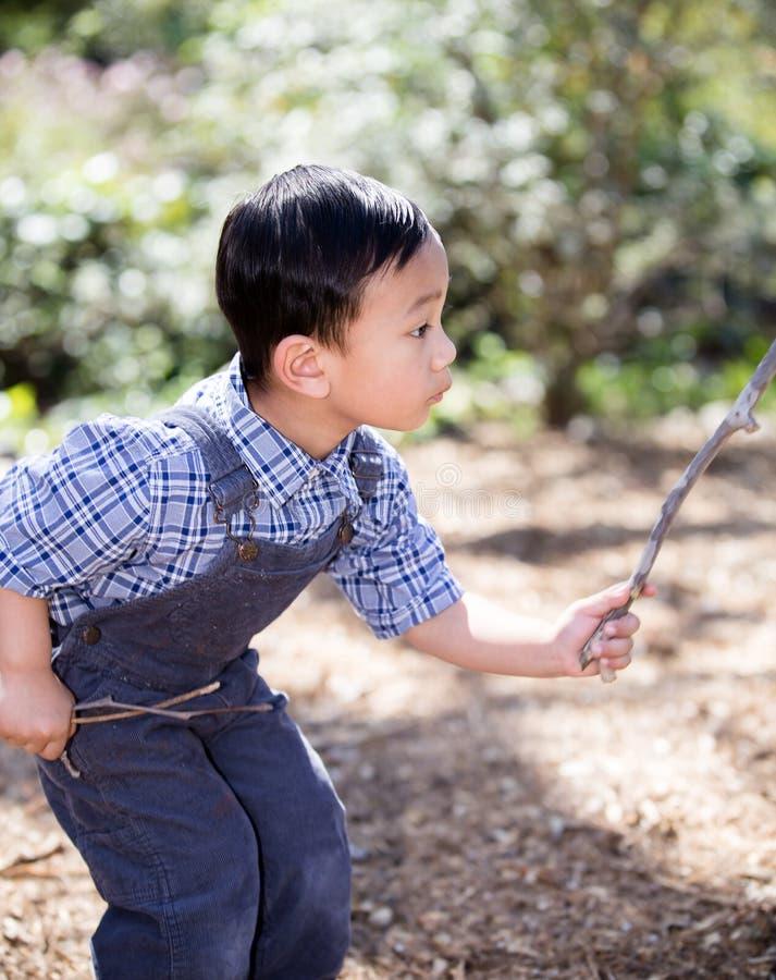 使用用棍子的亚裔男孩,当户外时 免版税库存图片
