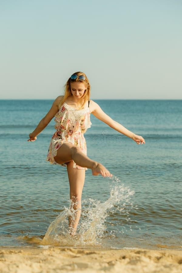使用用水的妇女佩带的礼服在海 免版税库存图片