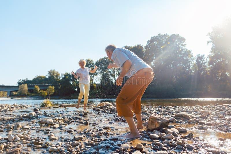 使用用水的滑稽的资深夫妇在河在一个晴天 免版税库存图片
