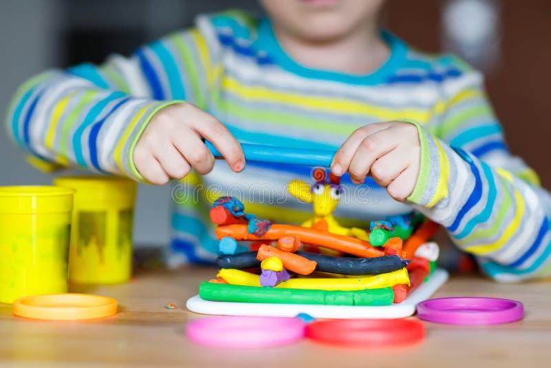 使用用面团,五颜六色的塑造的comp的小孩的手 免版税库存图片