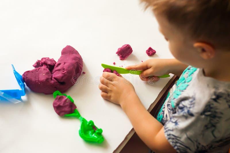 使用用黏土面团、教育和托儿概念的小男孩 库存图片