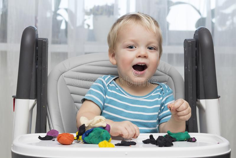 使用用黏土面团或塑造彩色塑泥、教育和托儿概念的滑稽的微笑的小男孩 库存照片