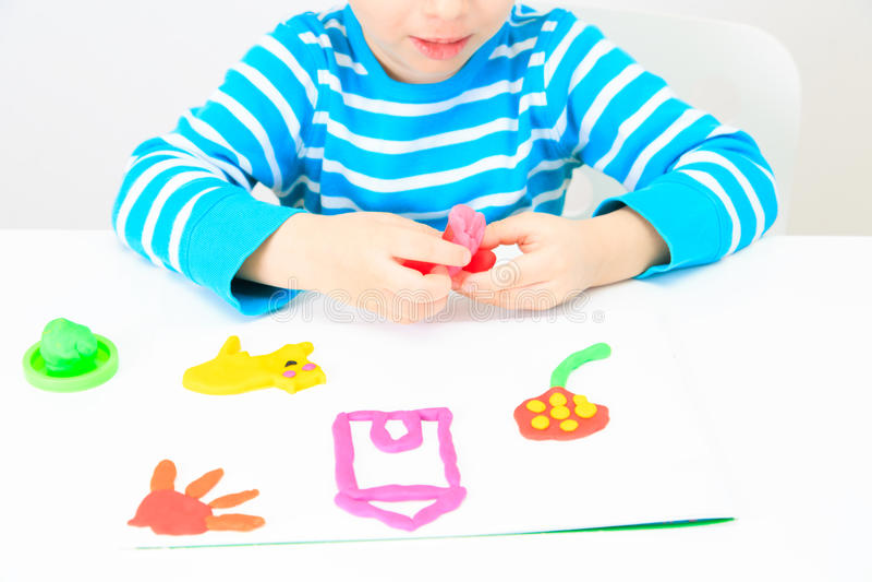 使用用黏土面团,教育的小男孩和 库存照片
