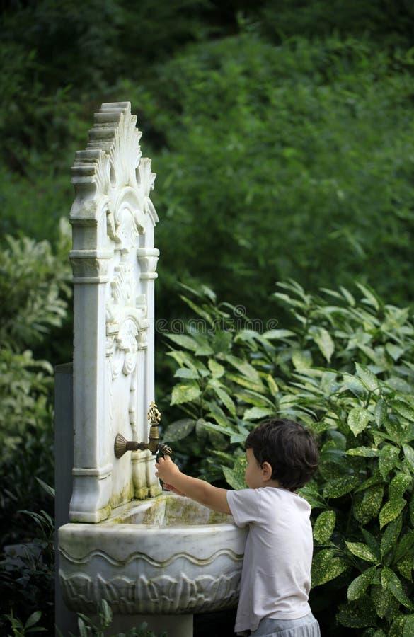 使用用从无背长椅样式经典之作fountai的水的小孩 免版税库存图片