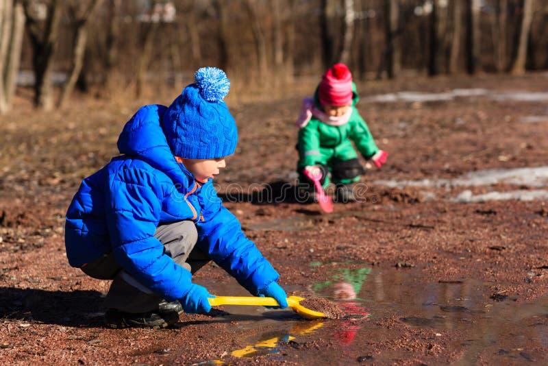 使用用水的小男孩和女孩在春天 库存照片