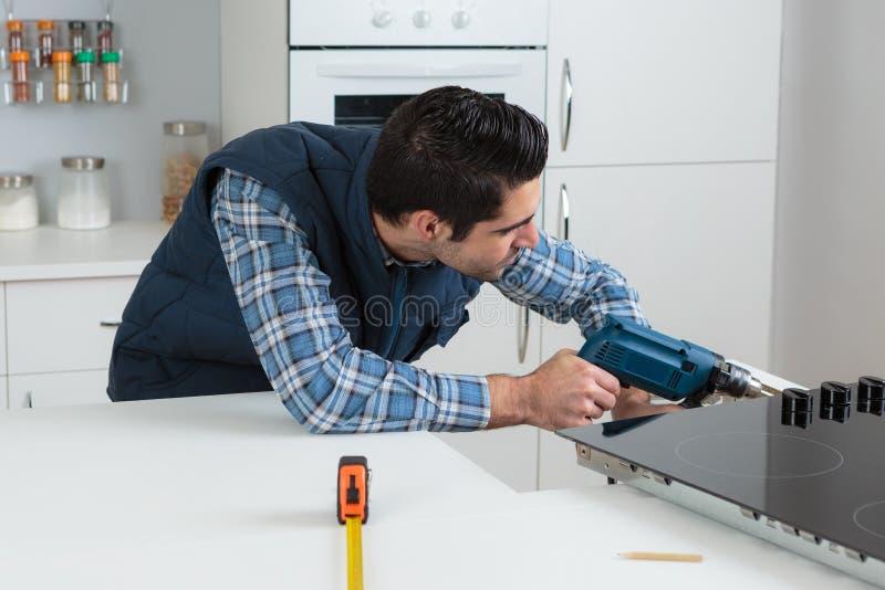 使用电动工具的人在住宅设置 免版税库存照片