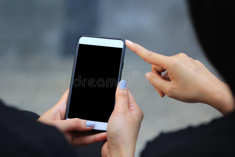使用电子小配件,键入的消息的妇女或检查在人脉的简短的新闻报道与她的朋友 免版税库存照片