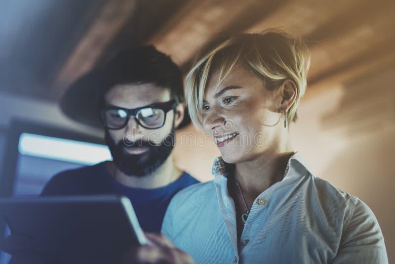 使用电子片剂的愉快的家庭夫妇在客厅在家 做交谈与的眼睛玻璃的有胡子的人 库存照片