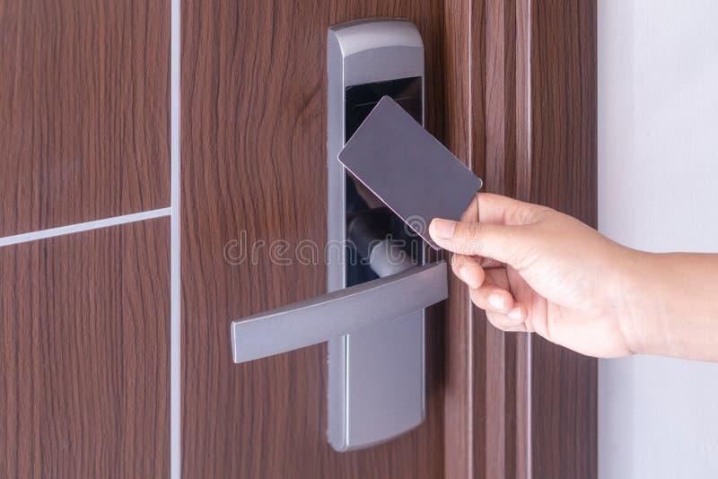 使用电子聪明的不接触的钥匙卡片的手为在旅馆或房子里打开门 免版税库存图片