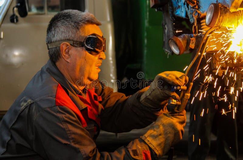 使用电弧金属焊接,运转的焊工在生产进行焊接的工作 免版税库存图片