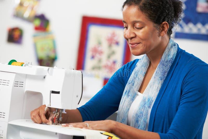 使用电缝纫机的妇女 免版税库存照片