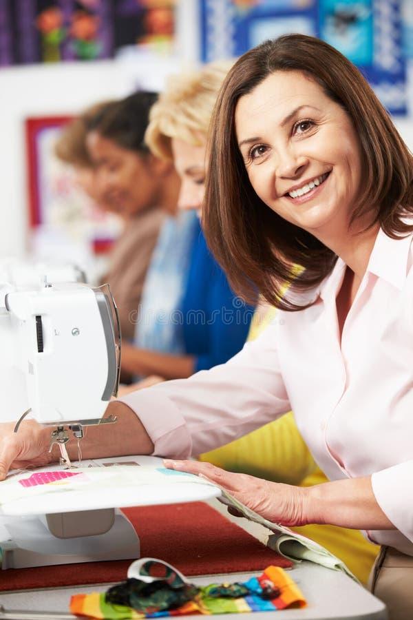 使用电缝纫机的小组妇女在类 库存照片