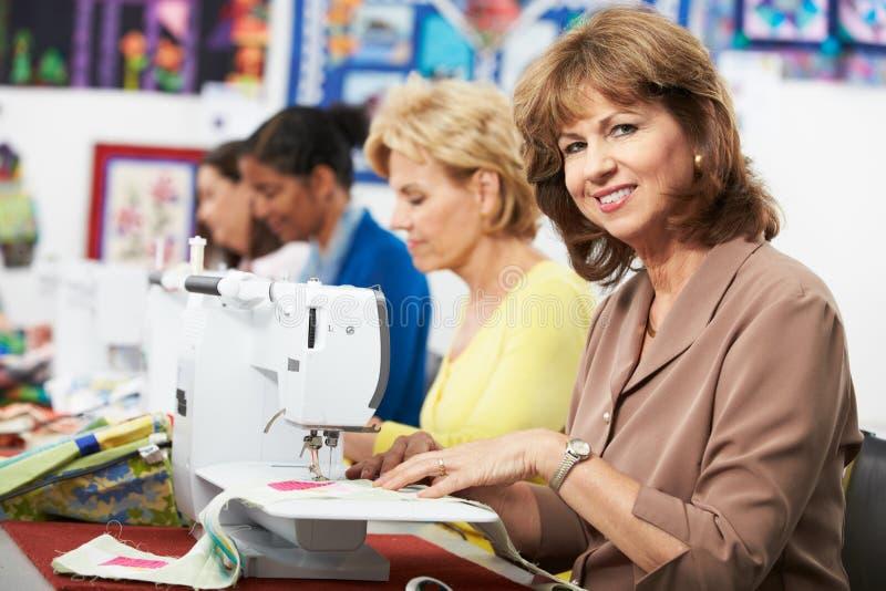使用电缝纫机的小组妇女在类 免版税图库摄影