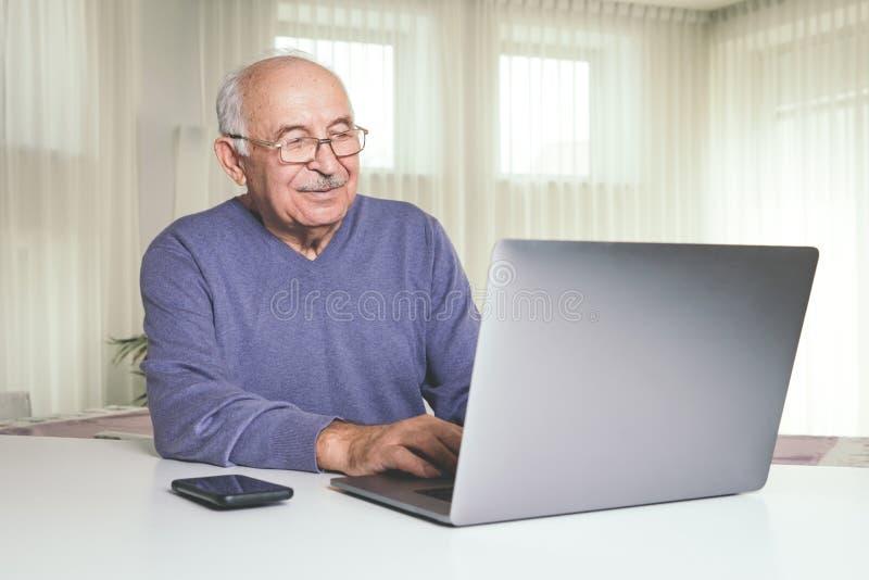 使用电脑技术的退休的人在家 免版税库存照片