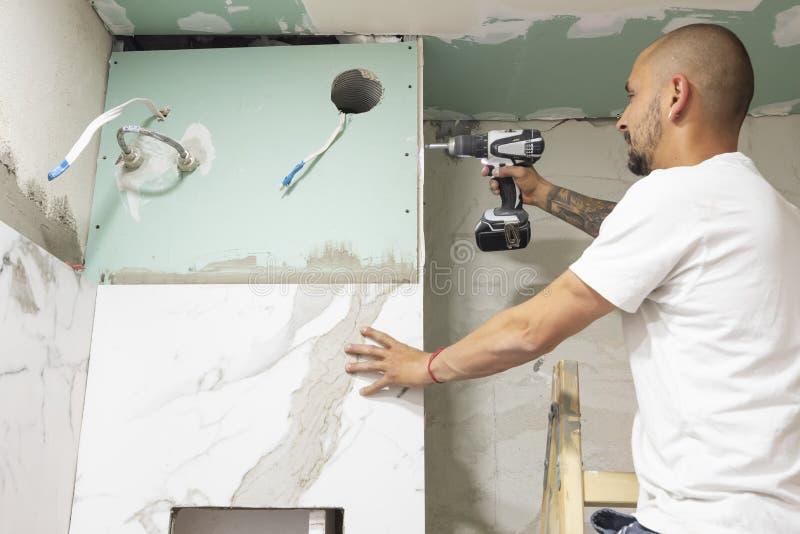 使用电螺丝刀的水管工 卫生间整修概念 有间隔号和灰色水泥墙壁的大理石瓷砖 免版税库存图片
