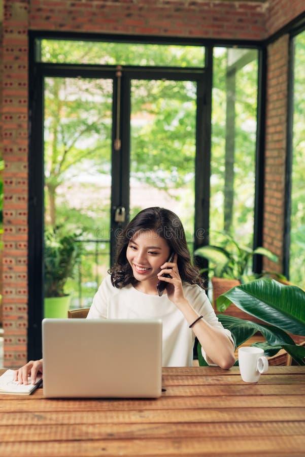 使用电话和膝上型计算机的确信的微笑的亚裔妇女 库存照片