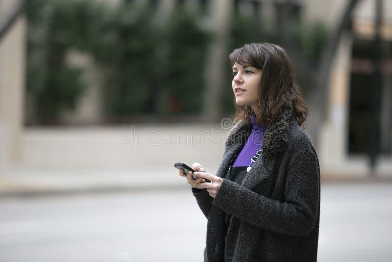 使用电话应用程序和等待的乘驾份额的妇女 库存图片
