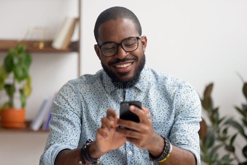使用电话流动应用程序的愉快的非裔美国人的商人在工作场所 免版税图库摄影