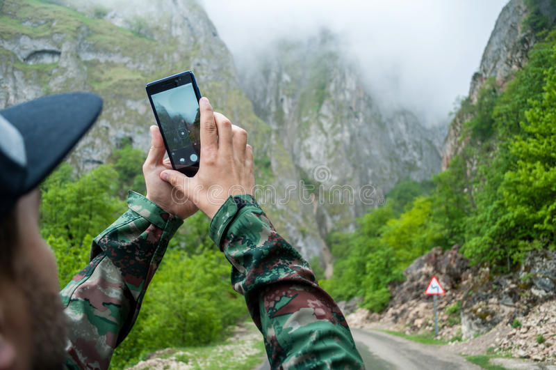 使用电话流动采取的照片山景的特写镜头手在早晨 库存图片