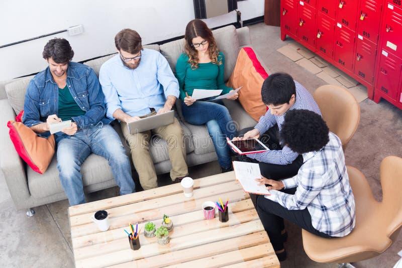 使用电话片剂计算机的人运转的办公室坐的沙发 库存图片