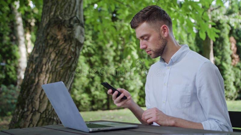 使用电话的一个年轻人在公园 免版税库存图片