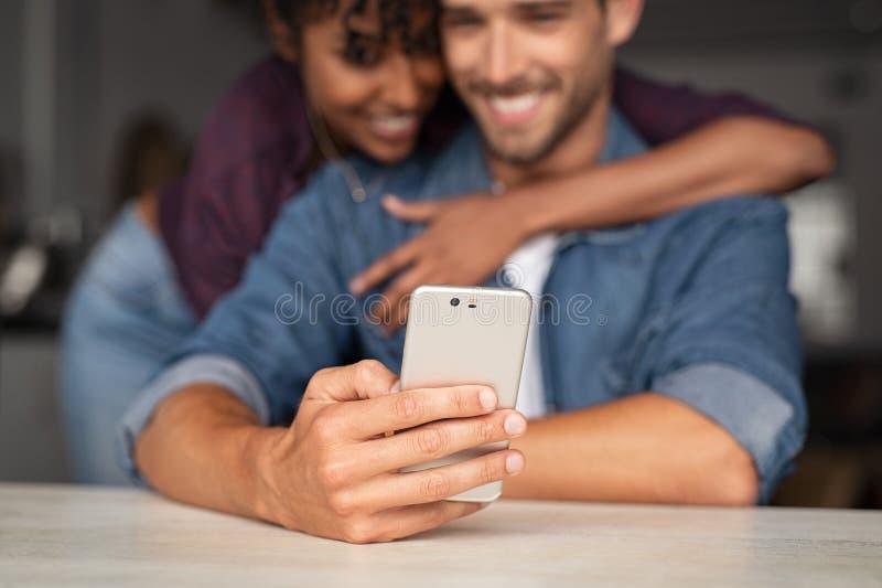 使用电话的不同种族的夫妇 库存图片