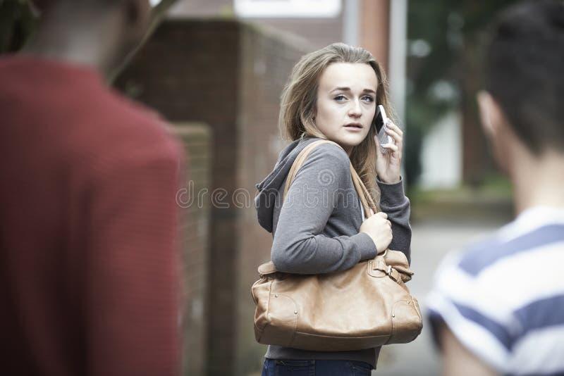 使用电话的十几岁的女孩,她在回家感觉威逼 图库摄影