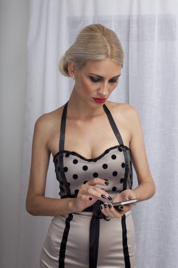 使用电话的可爱的妇女 免版税库存图片