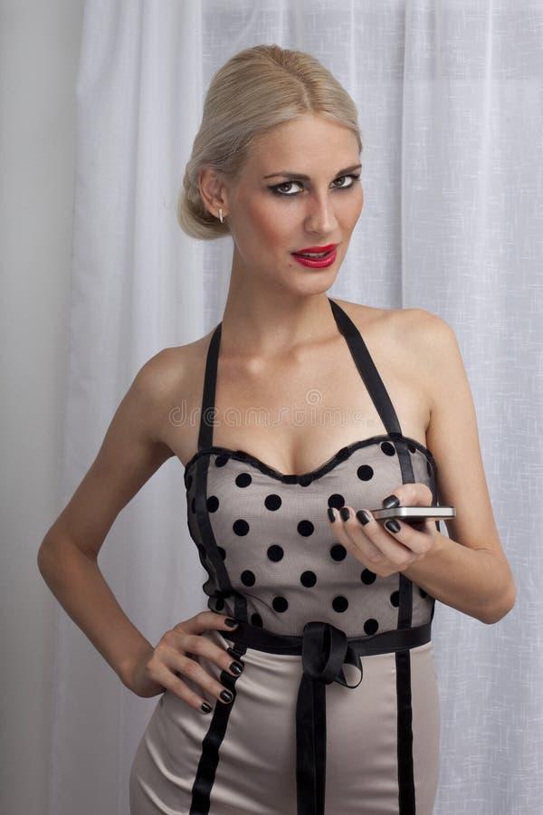 使用电话的可爱的妇女 免版税库存照片
