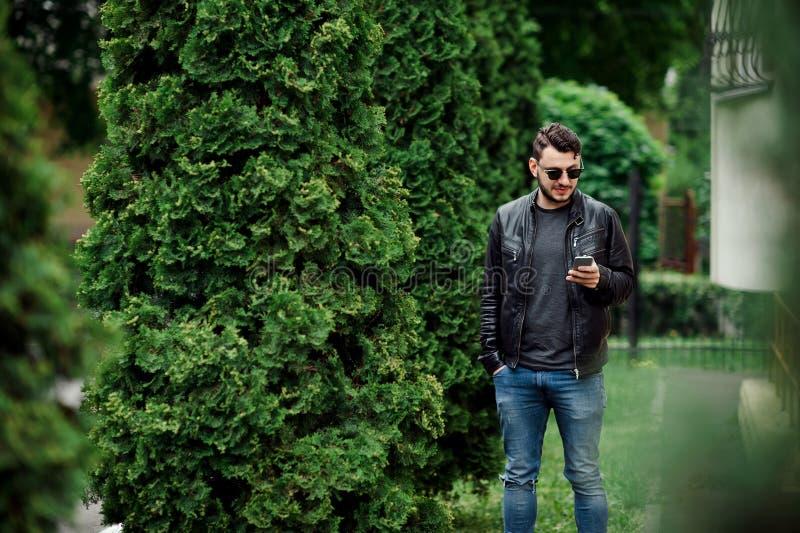 使用电话的可爱的年轻男孩在一个公园 免版税库存照片