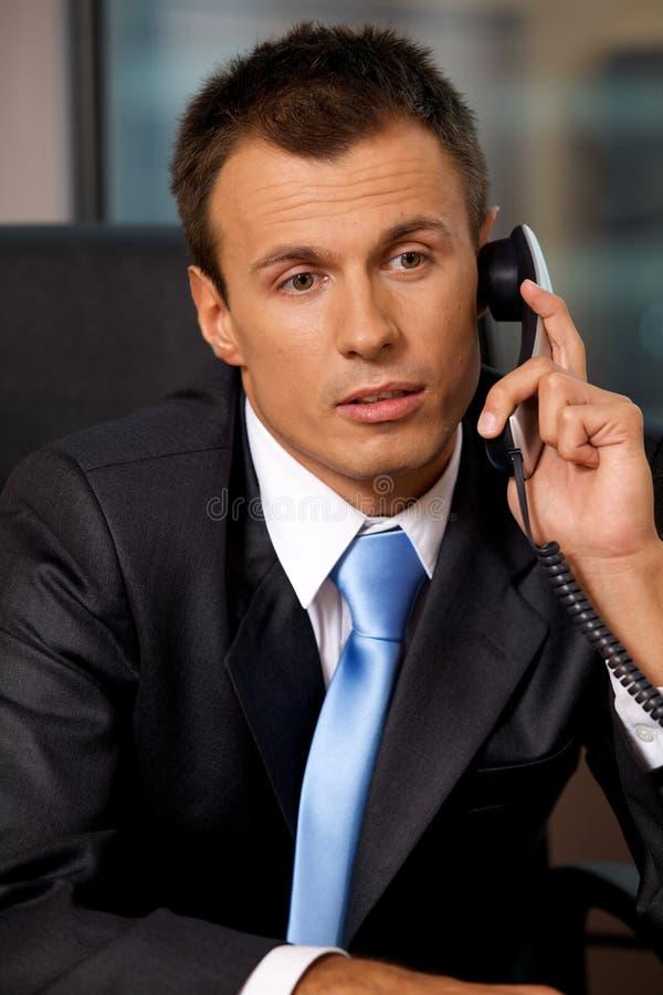 使用电话的商人在办公室 免版税图库摄影