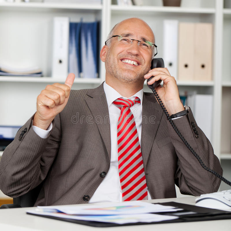 使用电话的商人,当打手势赞许时 库存图片