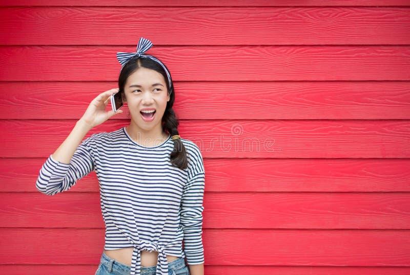 使用电话的女孩反对木背景 图库摄影