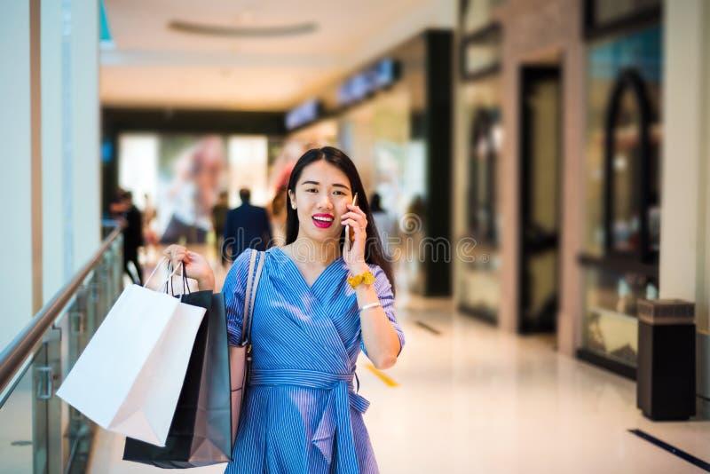 使用电话的女孩,当做购物时 免版税库存照片