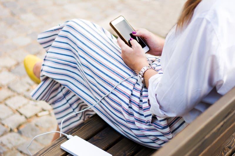 使用电话的女孩,当充电在力量银行时 免版税图库摄影