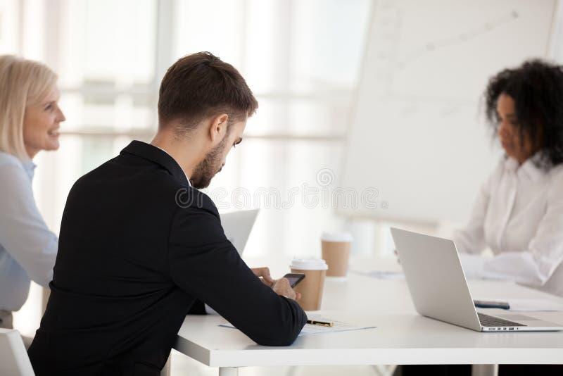 使用电话的女实业家在公司会议背面图 图库摄影