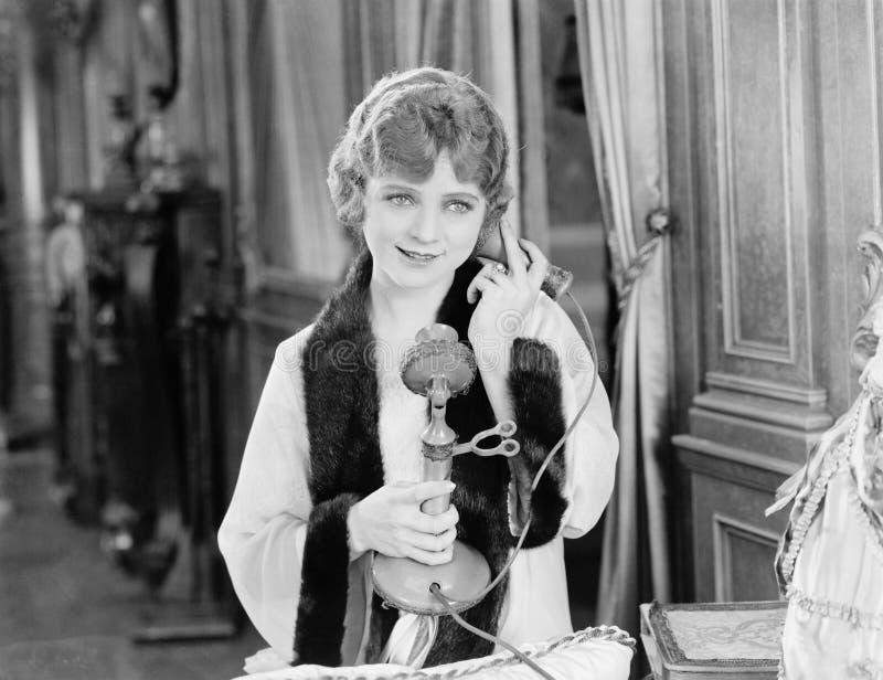 使用电话的妇女画象  免版税库存照片