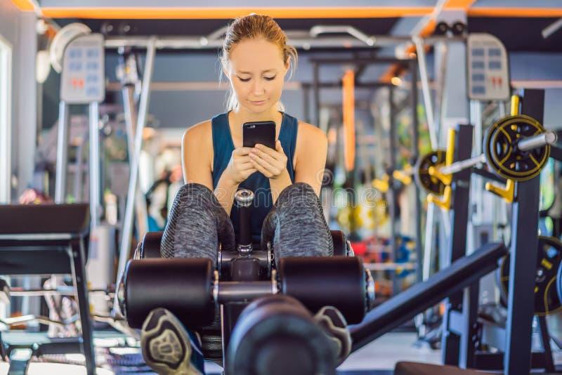 使用电话的年轻女人,当训练在健身房时 妇女坐行使拿着手机的机器 免版税图库摄影