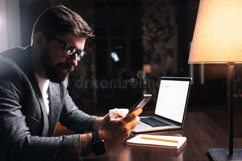 使用电话的年轻有胡子的商人,当坐由木桌在现代办公室在晚上时 工作移动设备的人们 免版税库存图片