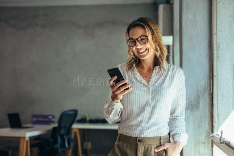 使用电话的微笑的女实业家在办公室 免版税库存照片