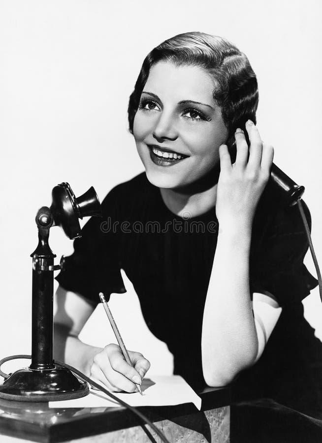 使用电话的微笑的妇女 免版税库存图片