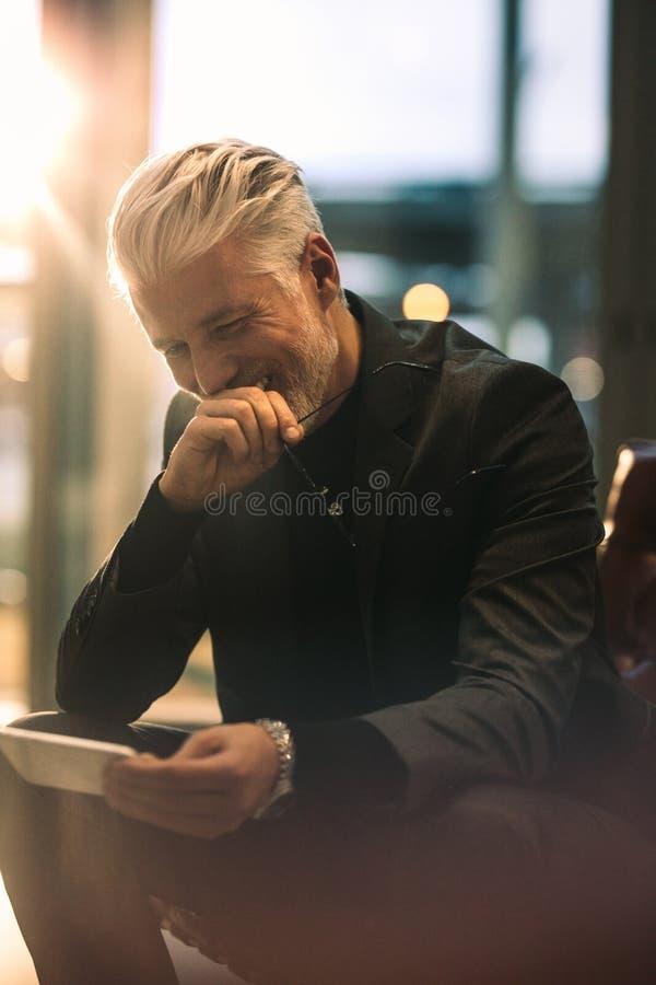 使用电话的成熟商人在办公室大厅 库存图片