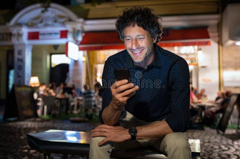 使用电话的成熟愉快的人在晚上 免版税图库摄影